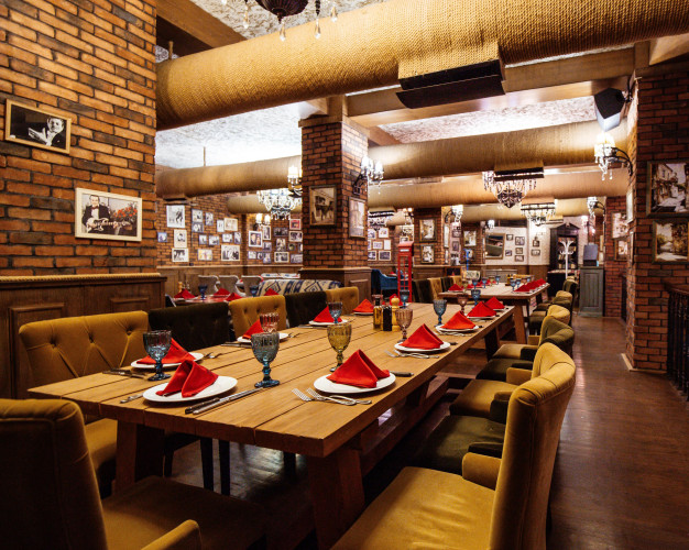 restaurant-hall-with-red-brick-walls-wooden-tables-pipes-ceiling_140725-8504